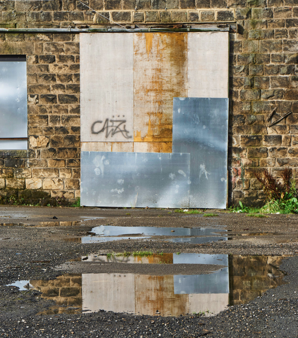 boarded wondow reflected in puddle