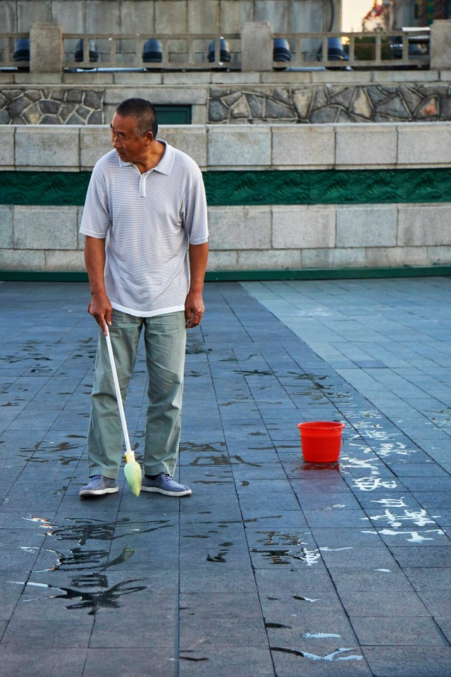 Man writing chinese characters on the street
