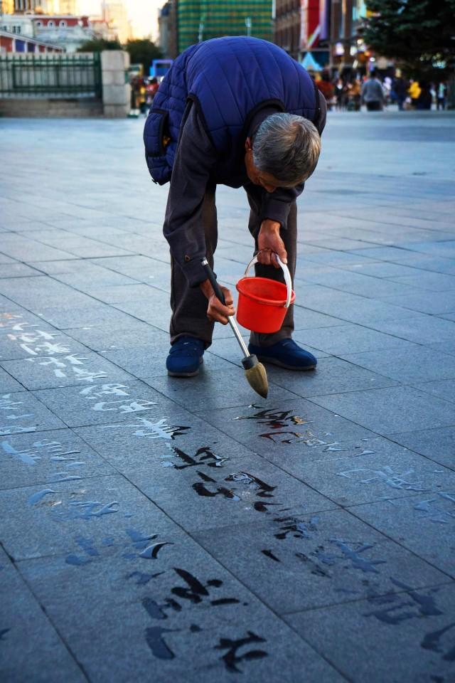 Man writing chinese characters on pavement